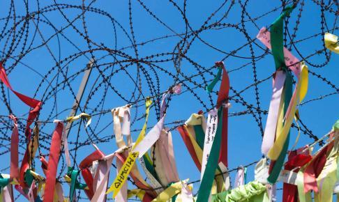 Farvestrålende stofstykker bundet omkring pigtråd ved DMZ - Risskov Rejser