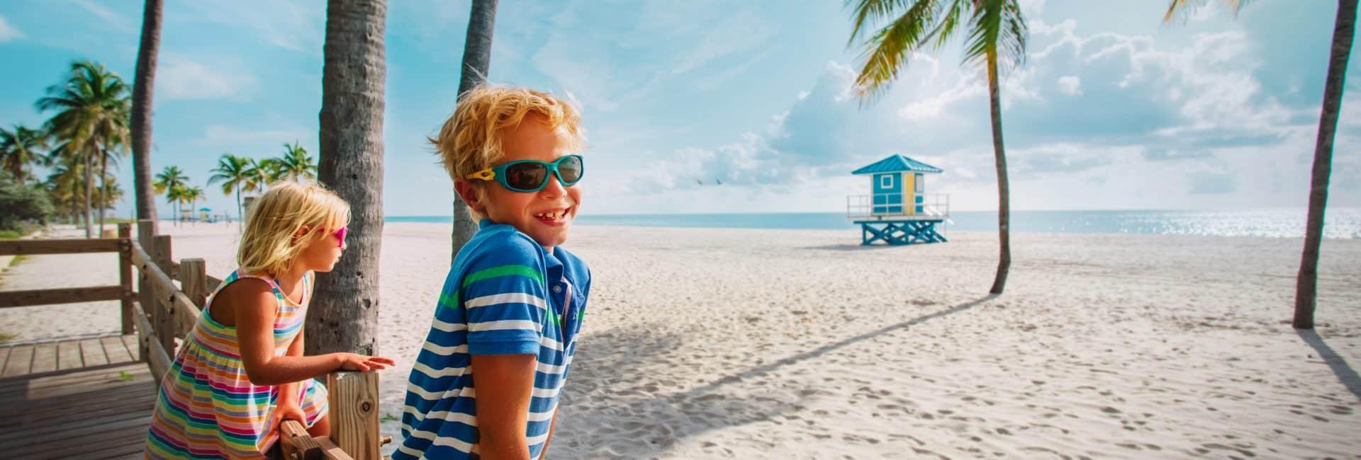 Glad dreng og pige på stranden i Florida i USA