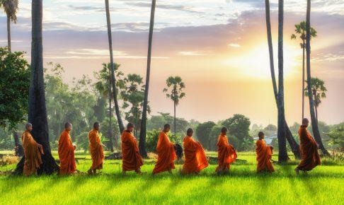 Buddhistiske munke i solopgang på vej for at modtage lokale donationer i form af bl.a. ris